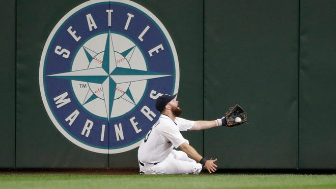 Seattle Mariners center fielder Dustin Ackley slides to make a catch of a deep fly ball from San Diego Padres' Will Middlebrooks during the sixth inning of a baseball game Tuesday, May 12, 2015, in Seattle.