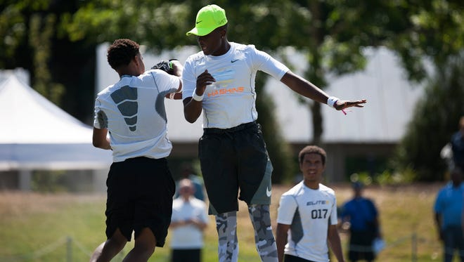 Quarterback Dwayne Haskins Jr., center,  celebrates with a receiver after throwing a touchdown pass during the morning practice at the Elite 11 camp in Beaverton, Ore.