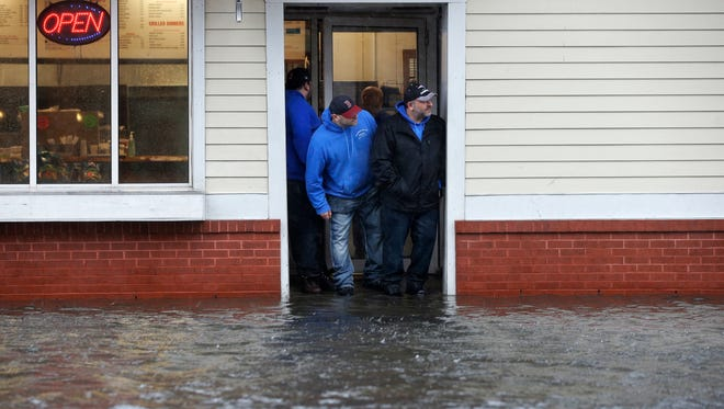 People stand at the entrance to a pizza shop as water floods a street, in Scituate, Mass., March 2, 2018.