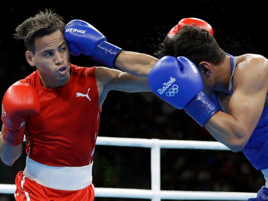 Cuba's Robeisy Ramirez, left, and Uzbekistan's Murodjon Akhmadaliev exchange punches during a men's bantamweight 56-kg semifinals boxing match at the 2016 Summer Olympics in Rio de Janeiro, Brazil, Thursday, Aug. 18, 2016. (AP Photo/Frank Franklin II)