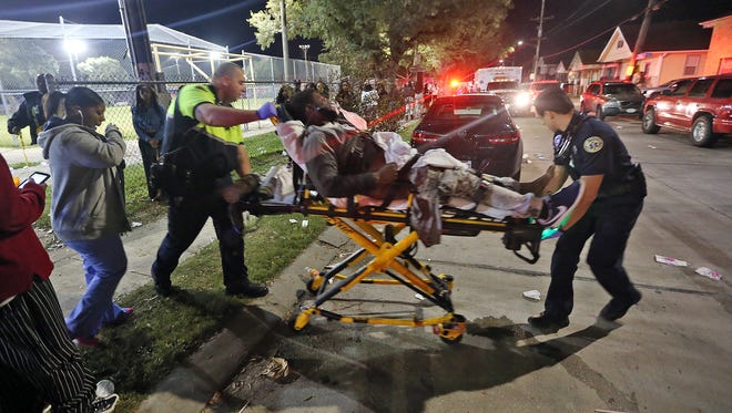Officials remove a man from the scene following a shooting in New Orleans' 9th Ward on Sunday. Police spokesman Tyler Gamble says police were on their way to break up a big crowd when gunfire.
