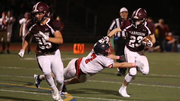 Harrison's Raymond Sanchez (23) is tackled by Eastchester's