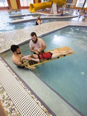 Joshua Apodaca, left, and Chris Behrems, right, work on pulling fellow lifeguard Ashley Kulek, onto a back board during a demonstration of how lifeguards would help someone who may have a spine injury at the Las Cruces Regional Aquatic Center.