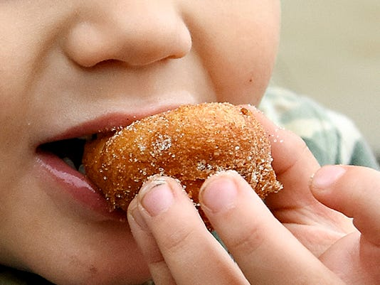 Gianni Corasaniti, 3, of York City, eats a mini doughnut from Here We Dough during York Flea, a street fair flea market, held in the 100 block of West Clark Avenue  in York, Pa. on Saturday, Oct. 3, 2015. Dawn J. Sagert - dsagert@yorkdispatch.com