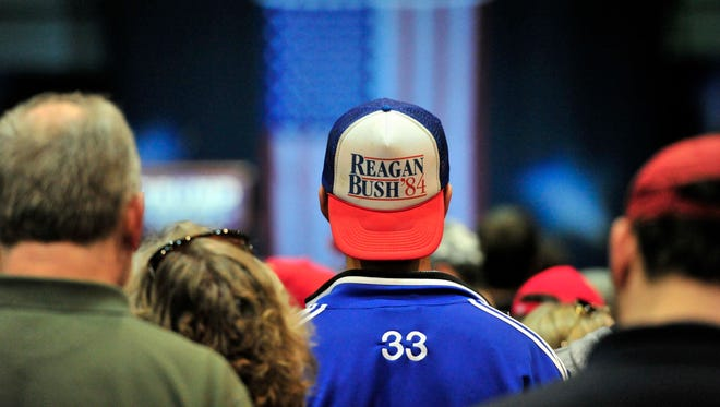 Ethan Diven, an aeronautical engineering student from Tuscaloosa, Ala, wears a Reagan-Bush cap as Donald Trump speaks during a campaign stop on Nov. 21, 2015 in Birmingham, Ala.