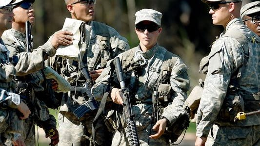 A female Army Ranger stands with her unit during Ranger School at Camp Rudder on Eglin Air Force Base, Fla.