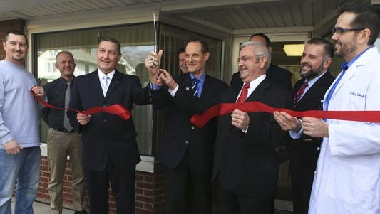 Michael Weinstein, AIDS Healthcare Foundation president, cuts through the ribbon with, at far right, Dr. William Cooke, the AHF medical director, during the public announcement Wednesday morning in Austin of a free HIV clinic and specialty pharmacy to treat HIV. Austin has been a small town hit hard by HIV infections. Around 184 people have contracted HIV in the small town's population of 4,200.