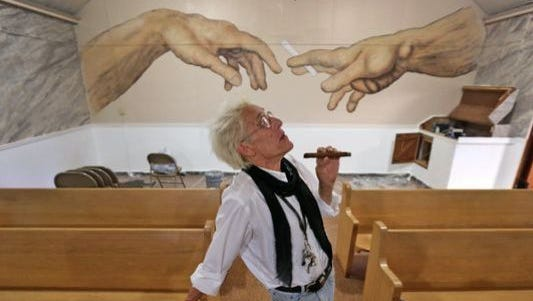 Bill Levin poses in the sanctuary at The First Church of Cannabis on June 23, 2015. The sanctuary includes a painting on the back wall of two hands passing a cannabis cigarette.