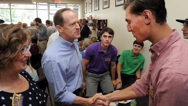 U.S. Sen. Pat Toomey, left, chats with teenagers Blake Wade, left and twin brother Logan, and Nick Spinelli, right, at the Cambria County Republican headquarters in Johnstown, Pa., where he stopped to meet with supporters on the campaign trail, Tuesday, July 19, 2016. At far left is Jackie Kulbak, chairwoman of the county's Republican party. (John Rucosky/Tribune-Democrat via AP)