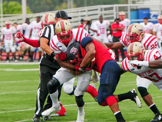 Shippensburg University running back Andrew Smith, center, powers his way through a trio of Seton Hill defenders on Saturday. The Red Raiders came up six points shy of the school record in a 64-14 win over the Griffins.