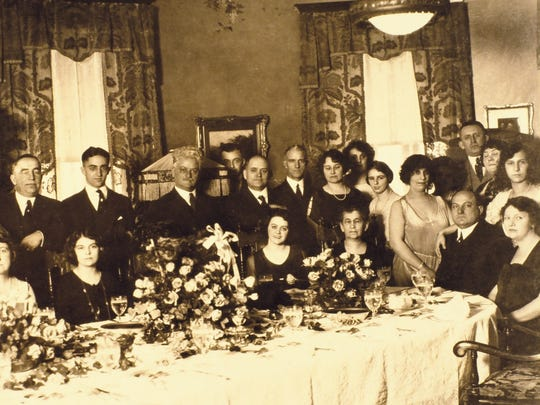 One of George Remus' lavish dinner parties at his Price Hill home. Remus is seated with his wife, Imogene, standing to his right, and his daughter with her arm on Remus' shoulder. Guests were usually given copies of the dinner party photos.