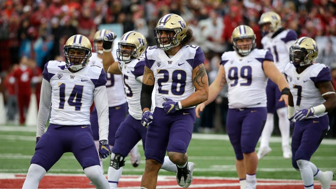 Washington players celebrate a fumble recovery Friday, Nov. 25, 2016, in Pullman, Wash.