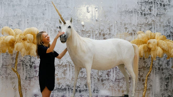 Kate Summers, Christie's Head of Sale for the auction strokes a model of a unicorn, Equus Caballus, during a press preview at Christie's auction rooms in London, Monday, Aug. 3, 2015.