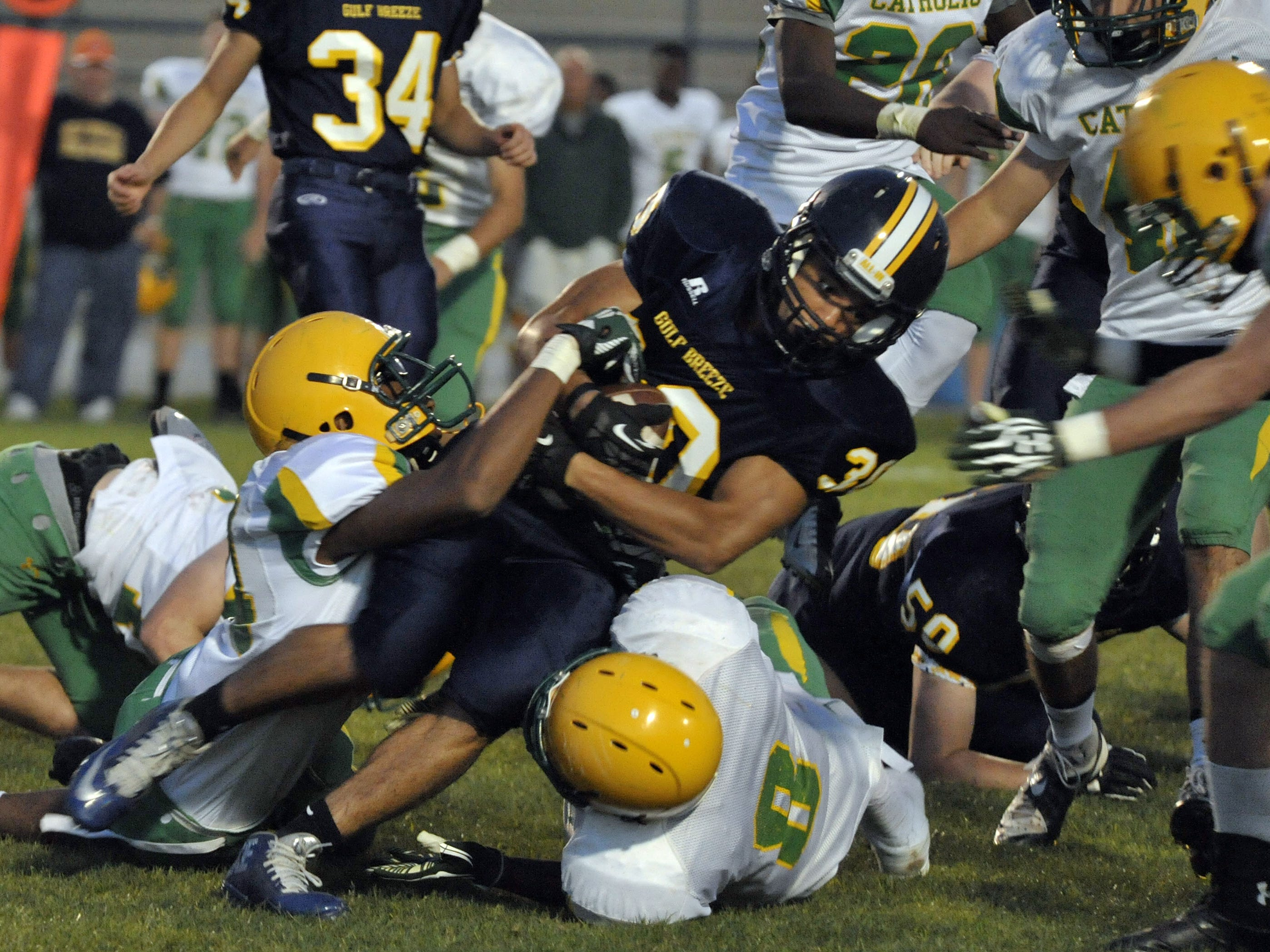 Catholic High drags down Chris Cain of Gulf Breeze during spring football action between the two teams earlier this year. Gulf Breeze will host Tate tonight in a kickoff classic.