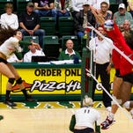 CSU outside hitter Alex Reid (5) attempts to spike a ball through New Mexico blockers Thursday at Moby Arena.