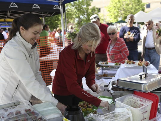 "Jamye Wood and Janet Neil make plates for customers in the Bert and Ernie's tent during last year's Alive@5 ""Taste of Great Falls."" The Downtown Great Falls Association announced the summer schedule recently."