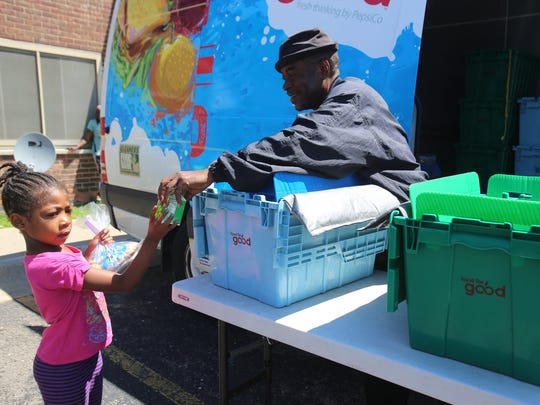 Raynard Liggins  gives out a lunch to Terriell Sawyer, 6, who lives with her family at the Sojourner Truth housing development.  Gleaners provides lunch every day to children through a mobile lunch service. It is  one of several programs Gleaners has running this summer. Photographed Wednesday, July 15, 2015.