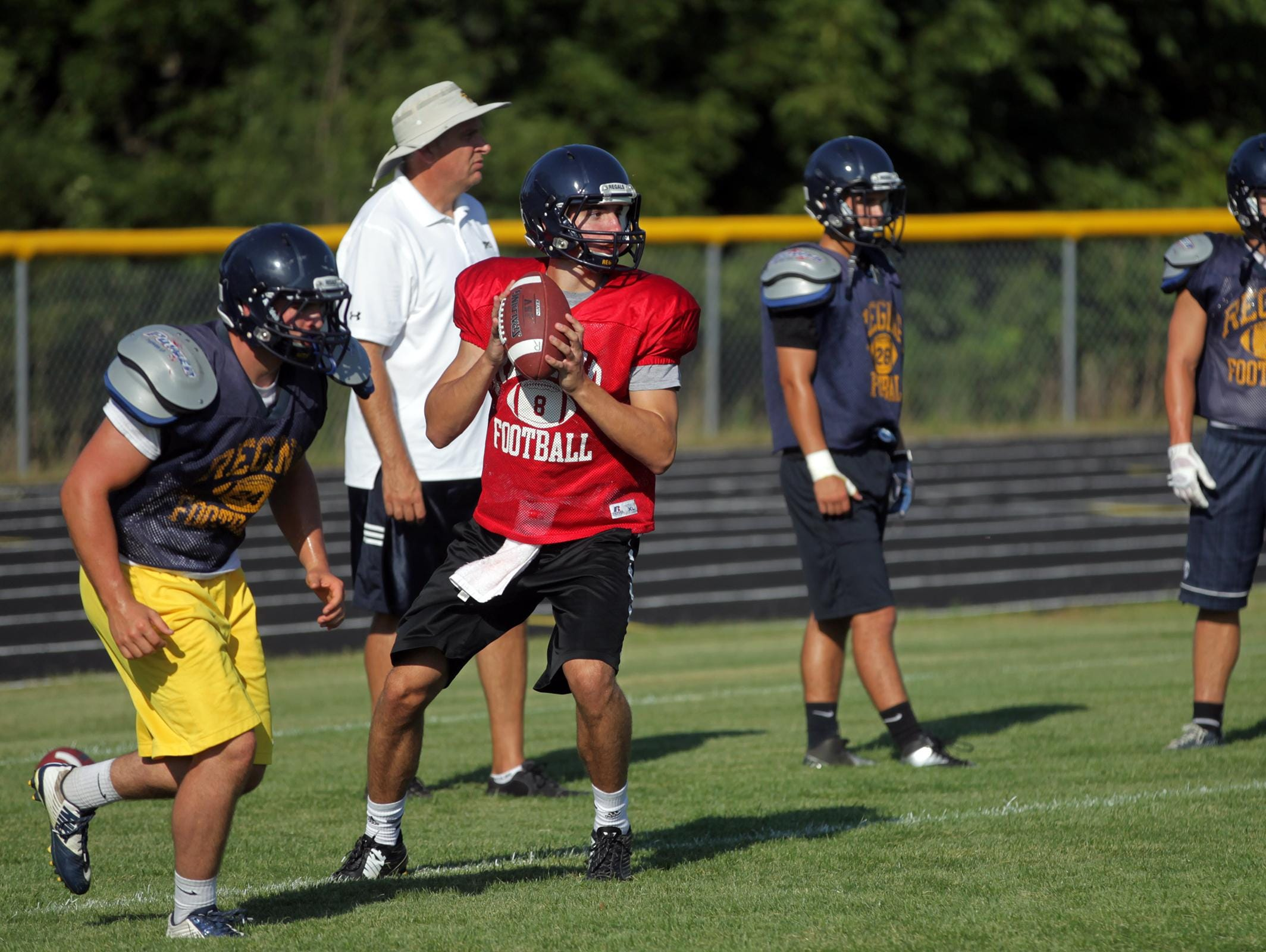 Regina quarterback Nathan Stenger looks for a receiver during practice on Wednesday, Aug. 12, 2015.