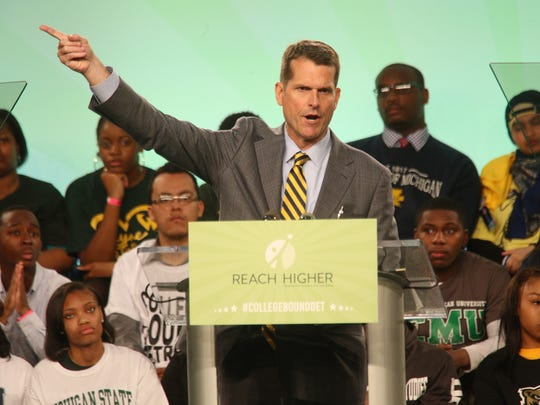 May 1, 2015: University of Michigan football coach Jim Harbaugh speaks before First Lady Michelle Obama, during the city-wide College Signing Day, as part of her Reach Higher initiative, hosted by Detroit College Access Network at Wayne State University in Detroit.