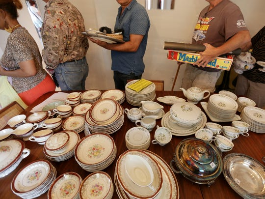 People shop an estate sale run by Americana Estate Sales that Cindy Brody hired to sell some of her mother's belongings in Southfield on Monday, August 3, 2015.