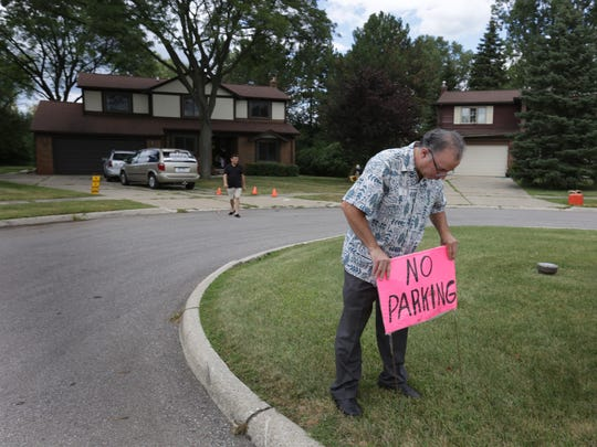 Mark Blondy of Americana Estate Sales places a no-parking sign in front of the home where he runs an estate sale in Southfield on Monday, August 3, 2015. Mark Blondy was hired by Cindy Brody to sell some of her mother's belongings.