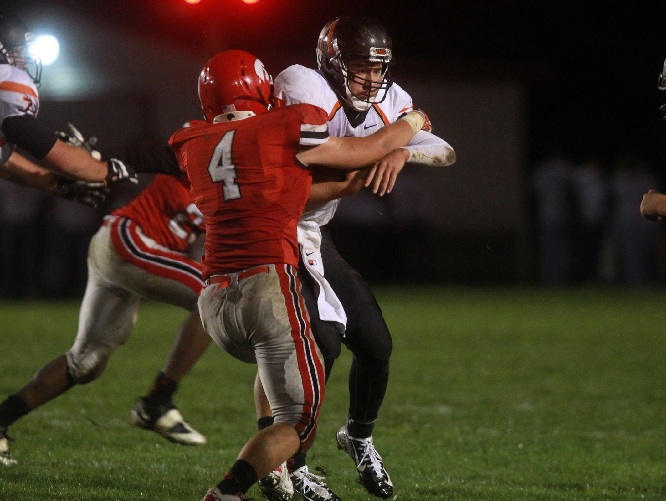 City High's Erick Fletcher stops Ames quarterback Michael Frankl during their game at City High on Friday, Sept. 12, 2014. David Scrivner / Iowa City Press-Citizen