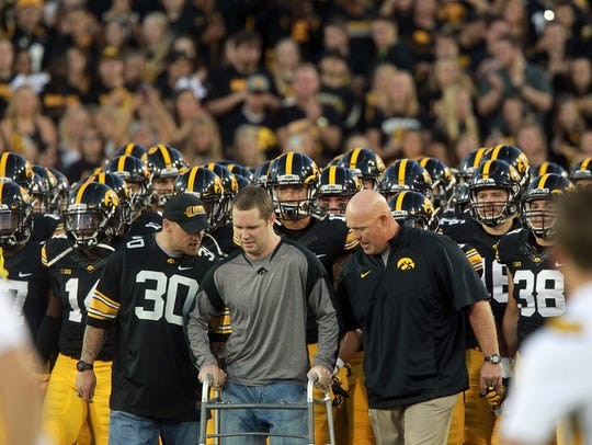 Former Colts linebacker Pat Angerer, left, helps former