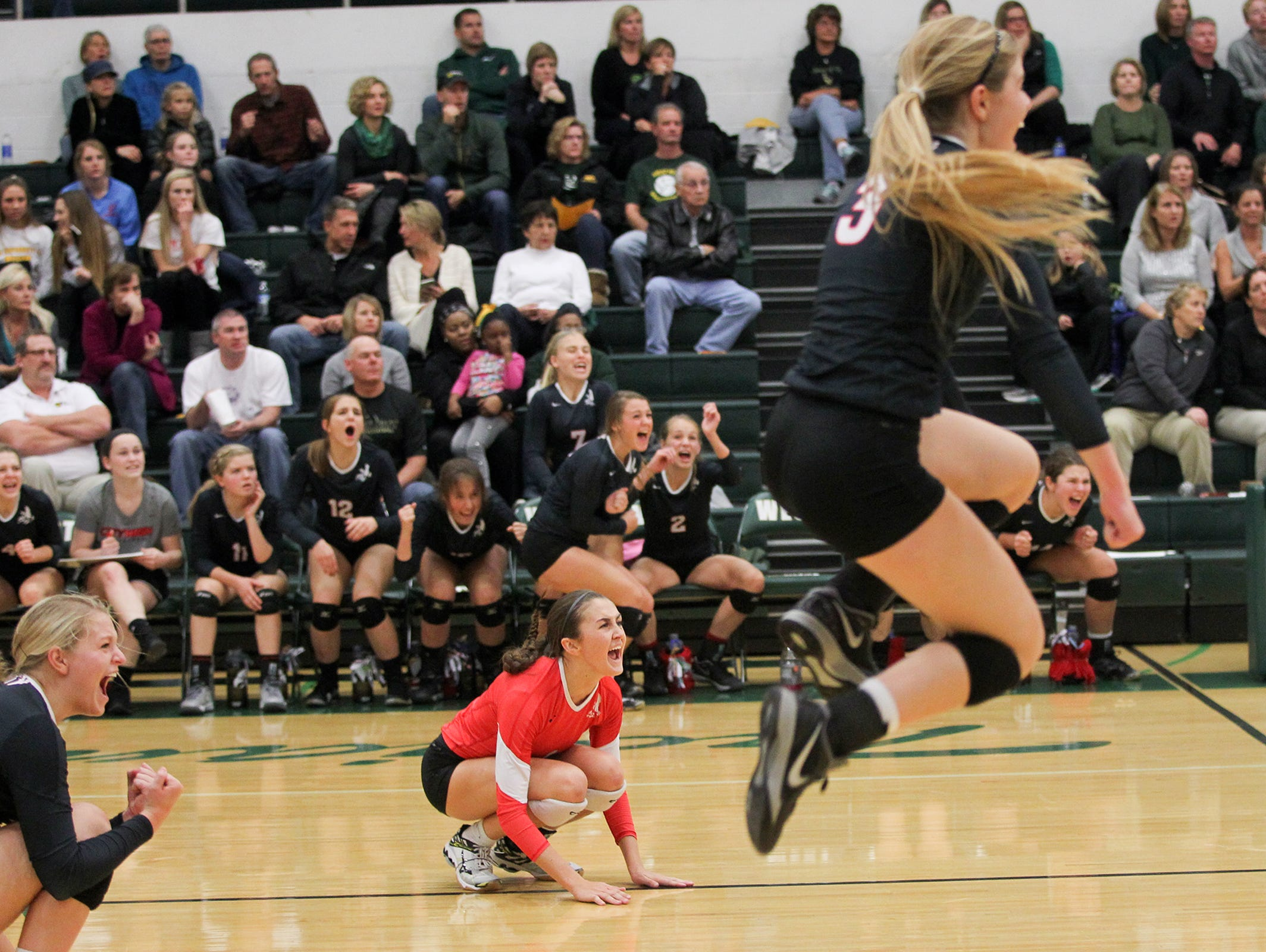 City High's Ashley Smith, center, celebrates a point during the Little Hawks' regional semifinal game at West High on Thursday, Oct. 29, 2015.