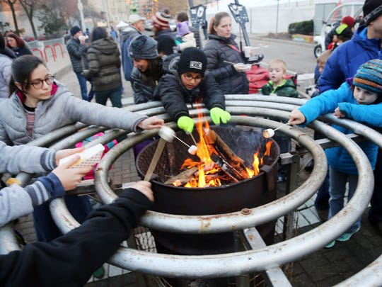 Families gather around the  fire to roast marshmallows prior to the Fifth Annual Lighting of the Menorah.
