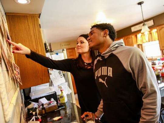 Brandon Randle, 18, looks at Christmas cards with Audra Granger, 32, on Tuesday, Dec. 22, 2015. Randle is from Raleigh, North Carolina, but goes to school at Battle Creek Central High School and lives with his football coach, Lorin Granger, and his family. Randle was going to return to Raleigh after his grandfather, who he was living with in Battle Creek, was in a car accident his junior year.