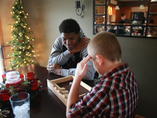 Brandon Randle, 18, plays a game with Kayden Granger, 9, at their home in Battle Creek, Mich. on Tuesday, Dec. 22, 2015. Randle is from Raleigh, North Carolina, but goes to school at Battle Creek Central High School and lives with his football coach, Lorin Granger, and his family. Randle was going to return to Raleigh after his grandfather, who he was living with in Battle Creek, was in a car accident his junior year.