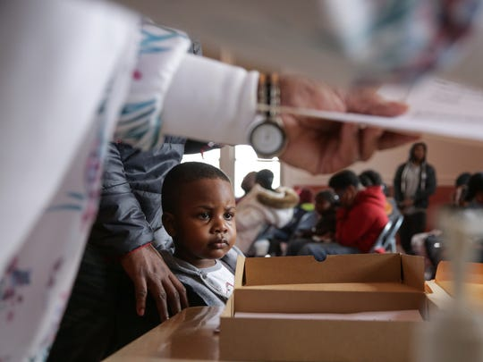 Jaylen Smith, 4, of Flint waits in line with his father, Keith Sanders, 25, of Flint to have blood samples taken to be tested for lead on Saturday, Jan. 23, 2016, at the Masonic Temple in downtown Flint.
