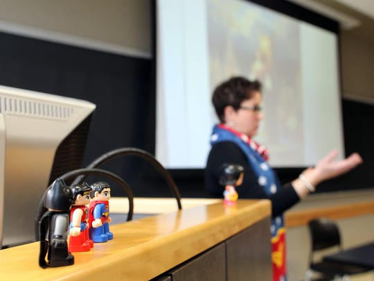"""Batman, Wonder Woman and Superman figurines stand on Anna Barker's podium as she leads discussion in her course, """"Wonder Woman Unleashed: A Hero for Our Times,"""" at the Adler Journalism Building on Thursday, March 3, 2016."""