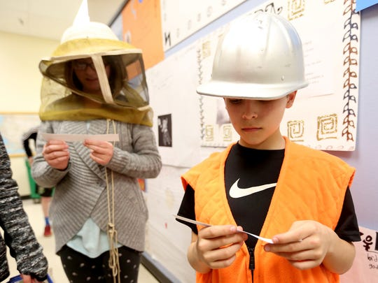 Fifth graders Tyler Lockhart, right, and Azie Arends dress as a forester and beekeeper, respectively, during a presentation on jobs in agriculture by the Oregon Agriculture in the Classroom Foundation at Myers Elementary School in West Salem on Tuesday, March 8, 2016.