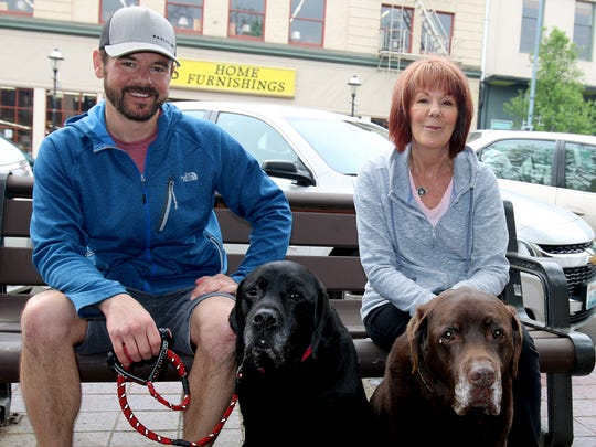 Tony Biasi with Cooper, a black lab, and Darla Biasi with Cooper's litter mate, Cody, a chocolate lab, came down to invite the public to the dogs' 13th birthday party Saturday at Pet Etc. in West Salem.