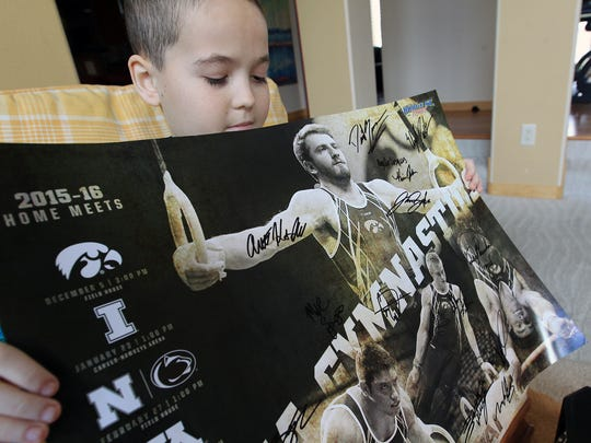 Calder Wills shows off a signed poster from Iowa's mens gymnastics team at his home on Thursday, April 7, 2016. At that time, he was an 11-year-old Hoover Elementary fifth-grader was diagnosed with T-Cell lymphoblastic lymphoma in February 2016. He passed away on Nov. 4, 2017.