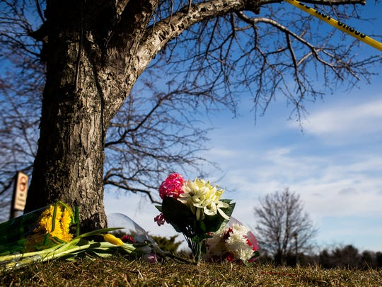 A memorial of flowers are seen resting near the scene