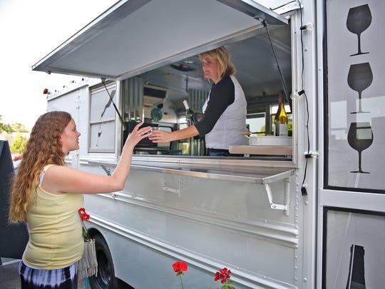 """Carmel """"mompreneur"""" Jenn Kampmeier serves wine to Becky Hinton from her new mobile wine bar, """"Vinny"""" The Vino Mobile Bar, on a stop at The Urban Chalkboard in Carmel on June 9, 2016."""