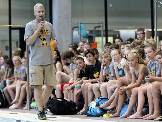 Iowa head coach Marc Long chats with campers during