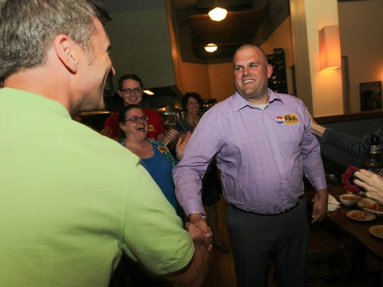 Iowa City Community School Board candidate Paul Roesler is congratulated by Matt Hayek as election results come in during a watch party at Motley Cow on Tuesday, July 19, 2016. Roesler won, according to unofficial results.