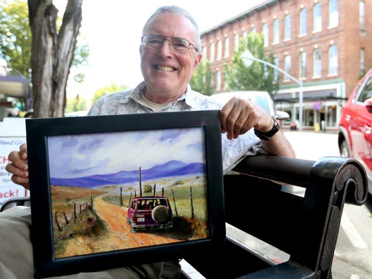 John Eells shows off a painting that will be part of a gallery show at the Salem Public Library during August during the Statesman Journal's Holding Court at the Court Street Dairy Lunch in downtown Salem on Tuesday, Aug. 2, 2016.