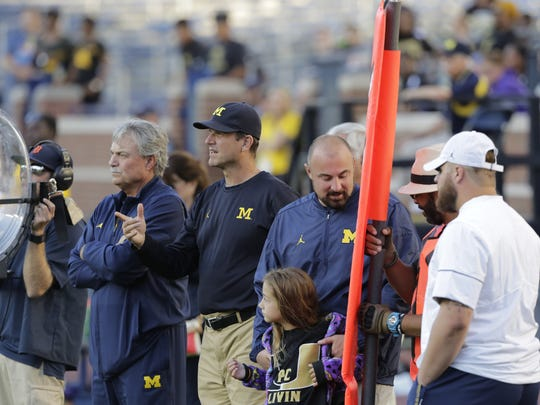 Chris Partridge, center, and Jim Harbaugh, left, watch during Paramus Catholic's (N.J.) 38-20 win over St. Frances Academy (N.J.) on Sept. 2, 2016 at Michigan Stadium.