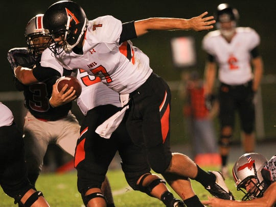 Ames quarterback Joe Evans breaks a tackle as he runs