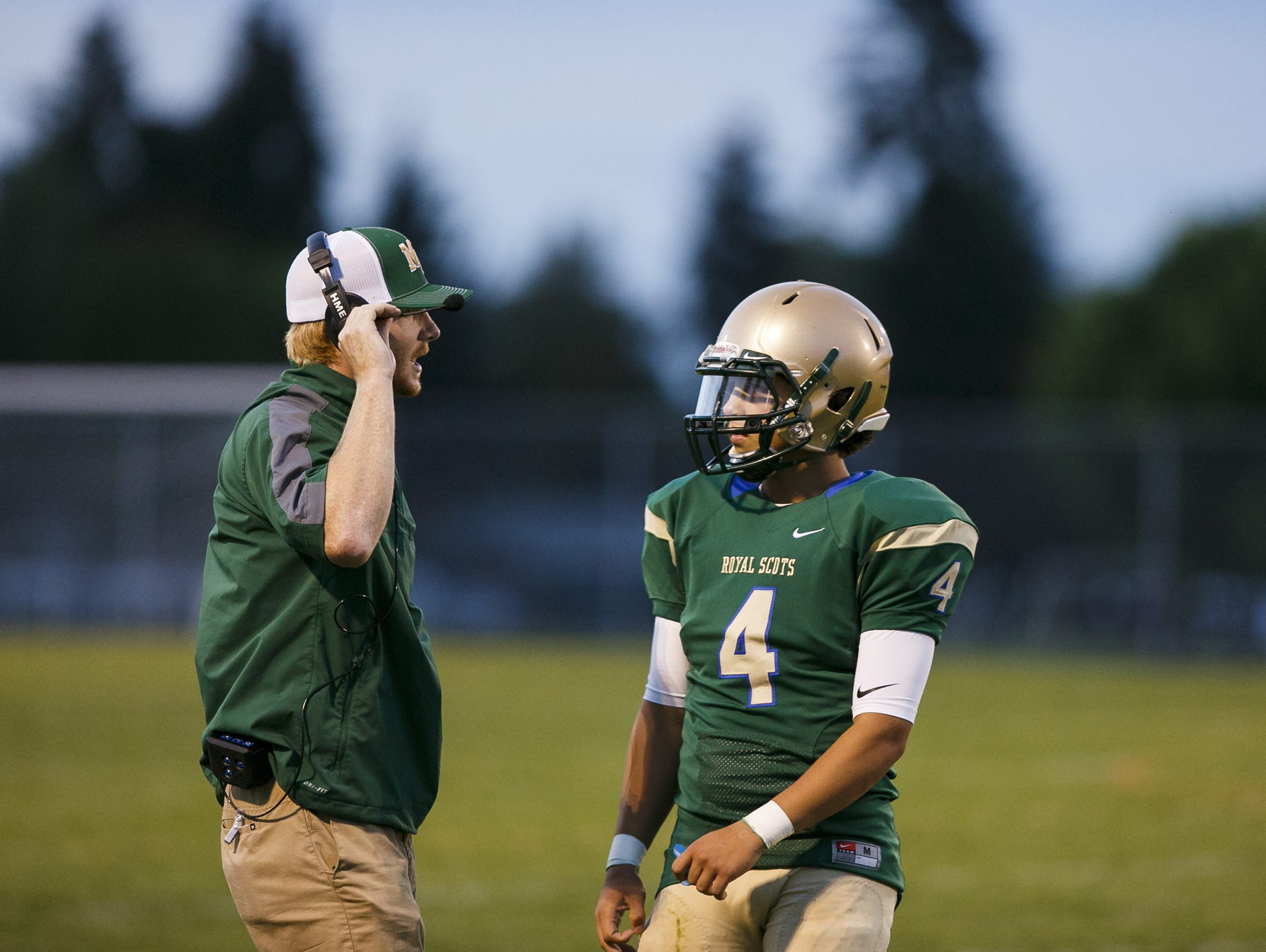 McKay head coach Josh Riddell speaks to quarterback Noah Tavera (4) during the Royal Scots' 43-0 victory over Forest Grove on Friday, Sept. 16, 2016.