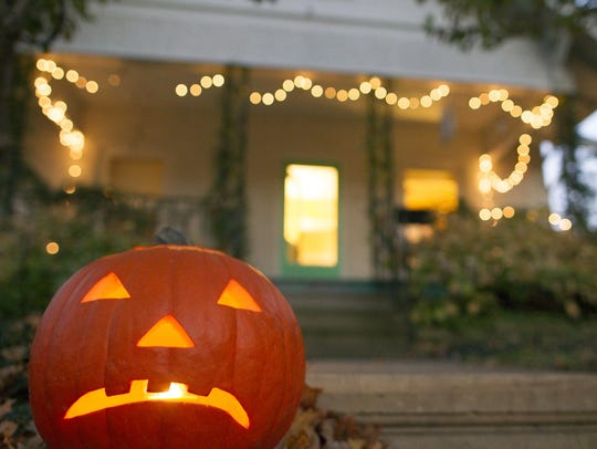 A carved pumpkin sits in front of a house on Friday,