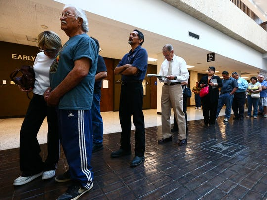Voters stand in line on the first day of early voting at the Nueces County Courthouse. Texas has kept its paper process for voter registration despite a growing national trend to move voter registration to more efficient online platforms.