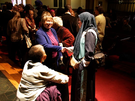 "Stella Harden of Detroit sits as Carol Cook Reid of Detroit, middle, shakes hands with Jennifer Alahi of Dearborn Heights. Michigan United joins a strong roster of service and faith organizations, Monday November 14, 2016 at the Central United Methodist Church in Detroit, to begin the work of advocacy under the new paradigm that Tuesday's election has brought to the community. ""I am in fear that all the rights we worked so hard for are going to be eroded"" said Harden, ""that's why I am here."" Mandi Wright/Detroit Free Press"