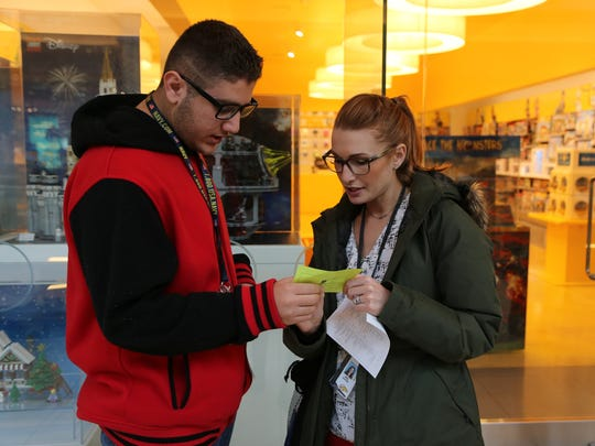Fadi Toma, 18, of Sterling Heights, shows Kaylee Viaene, a Special Education teacher at Sterling Heights High School, the paper that he was carrying with the information of the time the SMART bus would be passing the Somerset Collection on Tuesday, November 1, 2016.