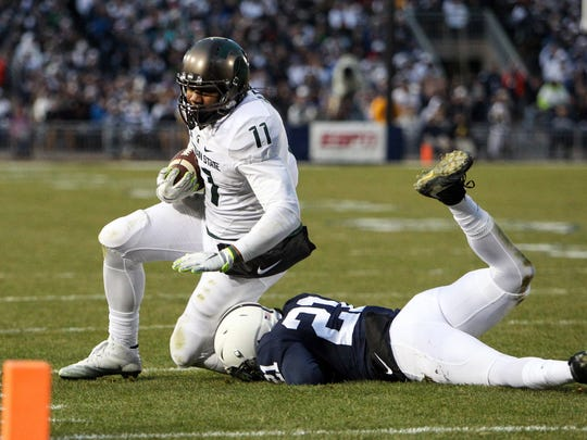 Nov 26, 2016; University Park, PA, USA; Michigan State Spartans tight end Jamal Lyles runs with the ball as Penn State Nittany Lions cornerback Amani Oruwariye attempts a tackle during the second quarter at Beaver Stadium.