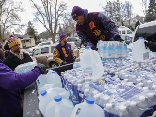 Kammal Smith of Troy, of Omega Psi Phi Fraternity, helps deliver donated water at Heavenly Host Baptist Church in Flint in January 2016.